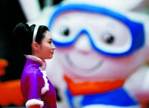 """(在第24届大冬会雪上项目颁奖仪式上,颁奖礼仪小姐站在吉祥物""""冬冬图片"""